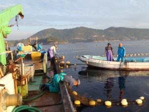 船員が第八光漁丸に乗り込み網を引き上げる準備。